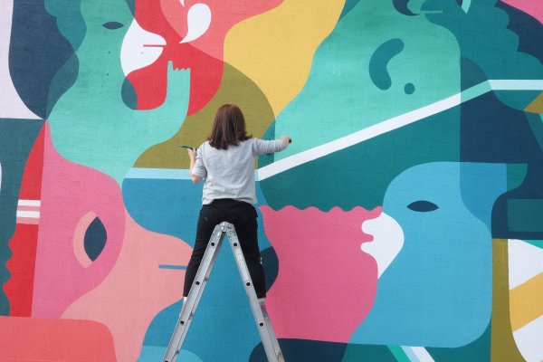 The artist in action for Ayajin primary school in 2014. It's easy to see why children might like the bright colors and cartoon shapes. Photo: Sixcoin.